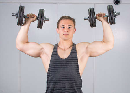 isolation tank: Man performing shoulders workout at the gym Stock Photo