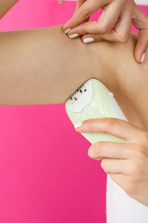 underarms: Woman epilates her armpit with an electric epilator device