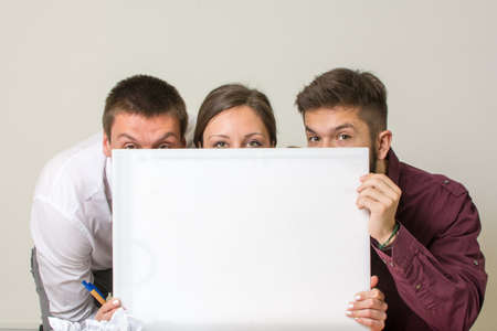team from behind: Our new project. Team hiding behind white board