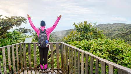 raised viewpoint: female hiker raising hands over a viewpoint