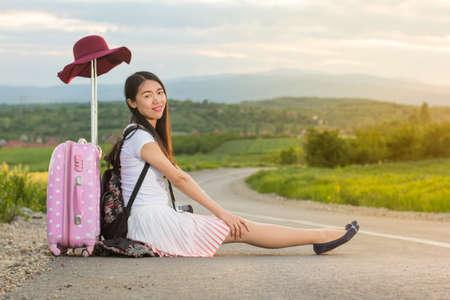 niñas chinas: chica solitaria sentado en la carretera junto a su maleta
