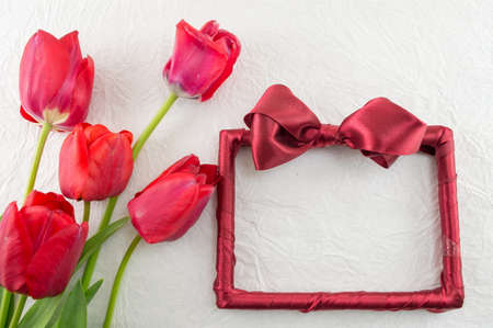 red tulips: Red tulips and a decorated photo frame a silk fabric