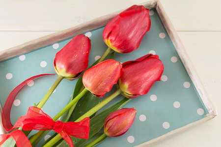red tulips: Red tulips in  a box on a wooden table Stock Photo