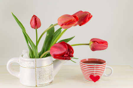 red tulips: Red tulips with a cup of tea on a wooden table Stock Photo