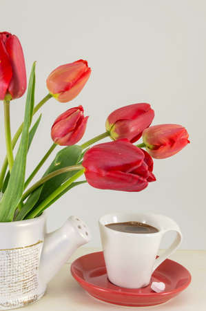 red tulips: Red tulips with a cup of coffee on a wooden table Stock Photo