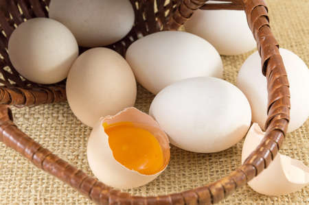 falling out: Fresh eggs falling out of awicker basket