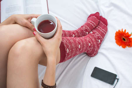 soft: Woman with a cup of tea listening to music in bed