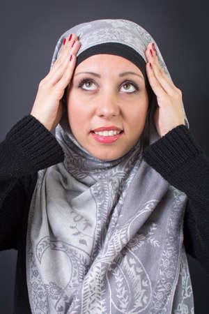 adjusting: Beautiful muslim woman adjusting her religious headscarf Stock Photo