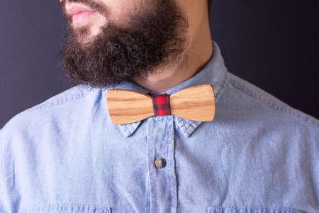hombre con barba: hombre con barba y una corbata de lazo de madera de cerca Foto de archivo