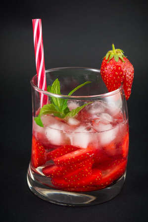 non alcoholic beverage: Strawberry juice in a crooked drinking glass against dark background Stock Photo