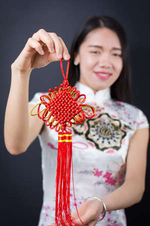 chipao: Beautiful asian woman holding a red Chinese knot Stock Photo