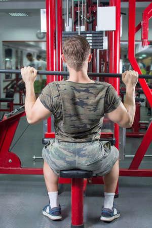 lats: Muscular man performing lat pulldown at the gym