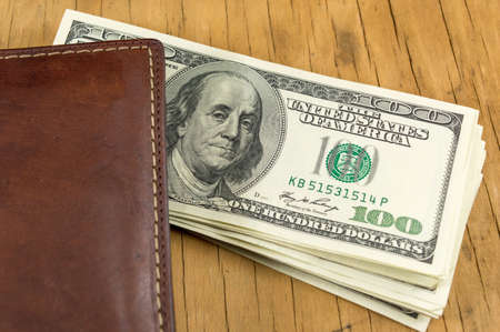 falling out: Leather wallet with dollar bills falling out Stock Photo