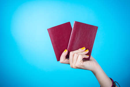 Womans hand holding a two red passports against blue background Stock Photo