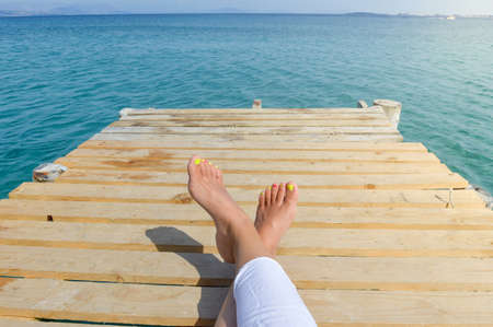 woman barefoot: Womans legs on a dock while relaxing by the seaside
