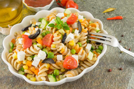 macaroni served with cheese vegetables and parsley. Colorful meal