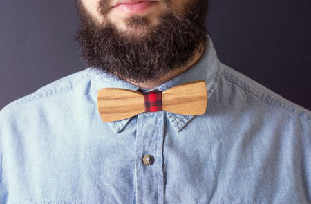 Bearded man with a wooden bow tie close up Imagens