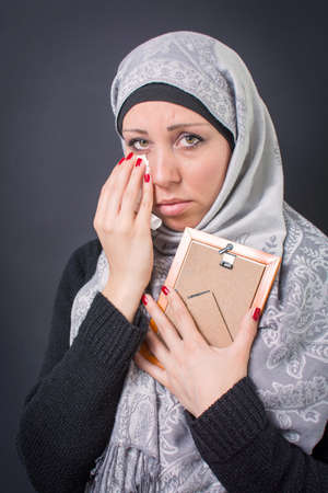 arab adult: Muslim woman moaning over an old photograph in a frame
