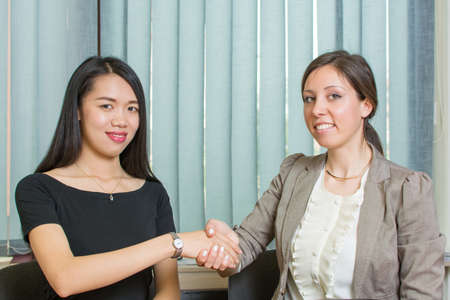 Two business woman shaking hands by the computer at the office