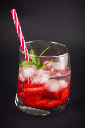 crooked: Strawberry juice in a crooked drinking glass against dark background Stock Photo