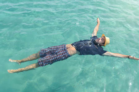 dressed up: Dressed up man floating on the water. Summer relaxation Stock Photo