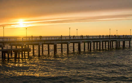 fense: PALANGA LITHUANIA - JUNE 13: Sunset view at the Palanga wooden dock. Palanga is the most popular summer resort in Lithuania Editorial
