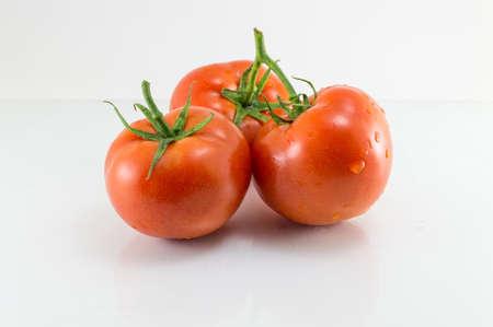 白い木製のテーブルに新鮮な生のトマト 写真素材