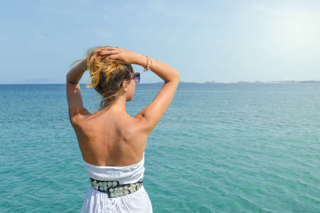 tanned woman: Tanned woman in dress facing seaside. Suumer vacation time