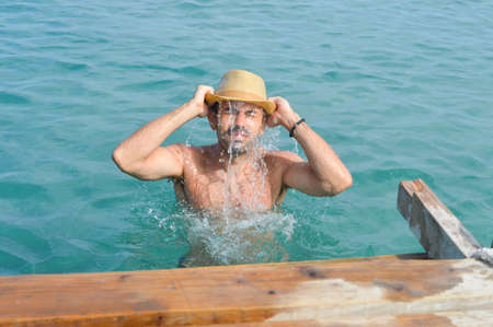 swimm: Young man in sea water wearing a hat full with water