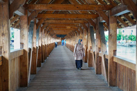 LUCERNE, SWITZERLAND - JUNE 13, 2016: Unidentified woman passing thru wooden famous bridge in Lucerne during daytime