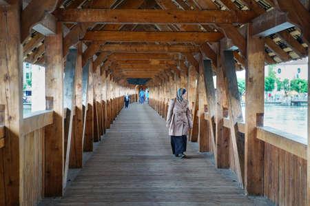 thru: LUCERNE, SWITZERLAND - JUNE 13, 2016: Unidentified woman passing thru wooden famous bridge in Lucerne during daytime