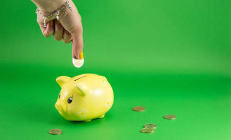 inserting: Woman hand inserting a coin into piggy bank Stock Photo