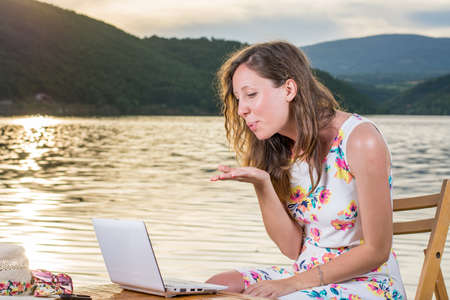 video call: Young woman having a video call by the lake