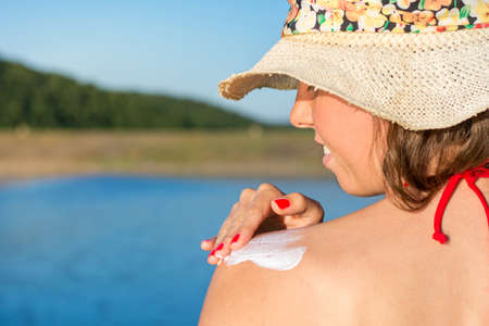 sun lotion: Young woman applying sun lotion on summer vacation