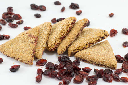 integral: Integral triangle cookies with red raisins on white table