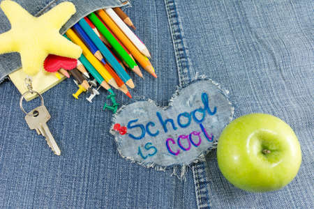 School is cool sign with creative learning objects on blue jeans