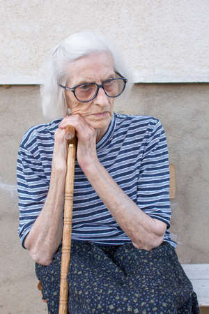 Senior women supporting on a walking cane outdoors