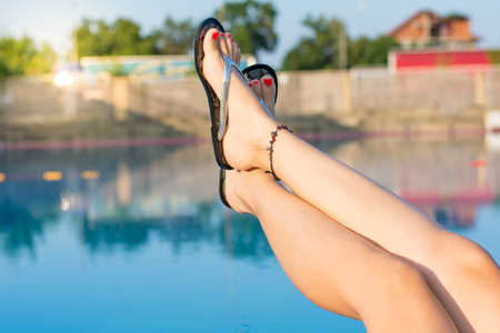 woman legs while enjoying at the swimming pool