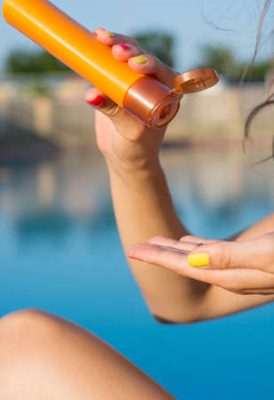 sun lotion: Woman applying sun lotion by the swimming pool Stock Photo