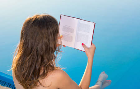 Girl reading by the swimming pool. Summer literature
