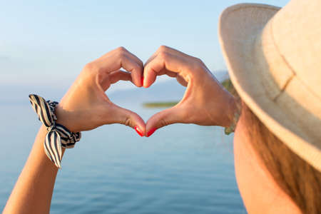 Woman hands making a heart shape at the beach Stock Photo
