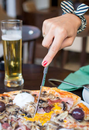 Woman hands while eating pizza at the restaurant Stock Photo