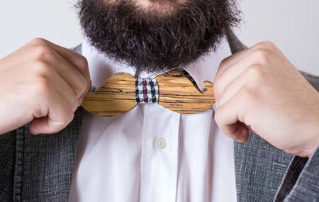 clothes interesting: Bearded man in a suit adjusting a wooden bow tie Stock Photo
