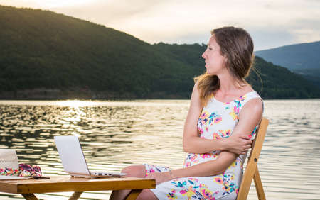 lap top: Pensive woman having with lap top computer by the lake Stock Photo