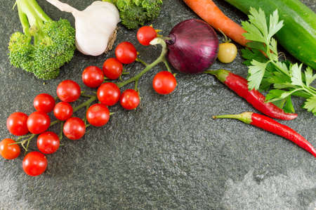 Raw tomato and red pepper on stone background Stock Photo