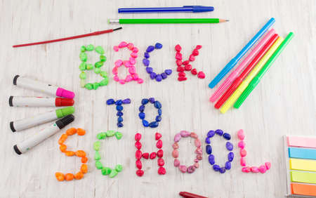 Back to school written with colorful stones and learning tools