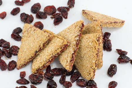 triangle shaped: Integral triangle cookies with red raisins on white table