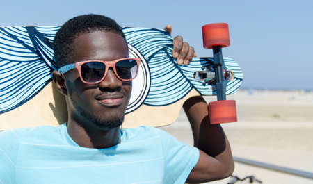 jamaican man: Young man outdoors with his skateboard