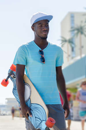 jamaican man: Young African American man with his skateboard