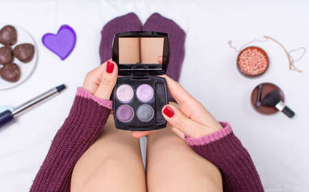 Girl applying eyeshadow in bed point of view Stock Photo